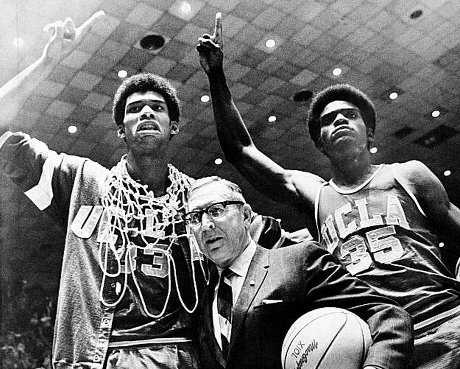 FILE - In this March 24, 1969, file photo, UCLA coach John Wooden is flanked by Sidney Wicks, right, and Lew Alcindor, draped with basket ropes, after the UCLA team beat Purdue 92-72 to win the NCAA basketball title for the third consecutive year, in Louisville, Ky. Wooden, college basketball's gentlemanly Wizard of Westwood who built one of the greatest dynasties in all of sports at UCLA and became one of the most revered coaches ever, has died. He was 99. Photo: AP
