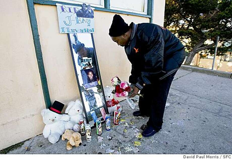 Larry Barefield,  the brother of murder victim Jonisha Tucker, puts flowers down on a memorial for her at her house in a Bayview-Hunters Point neighborhood on October 18, 2008 in San Francisco, California. Photograph by David Paul Morris / The Chronicle Photo: David Paul Morris, SFC