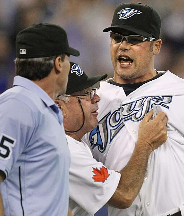 Toronto Blue Jays closer Kevin Gregg, right, has to be restrained by bench coach Nick Leyva, center, as Gregg yells at home plate umpire Angel Hernandez during ninth inning AL baseball action against the Tampa Bay Rays in Toronto Tuesday, June 1, 2010. Photo: Darren Calabrese, AP