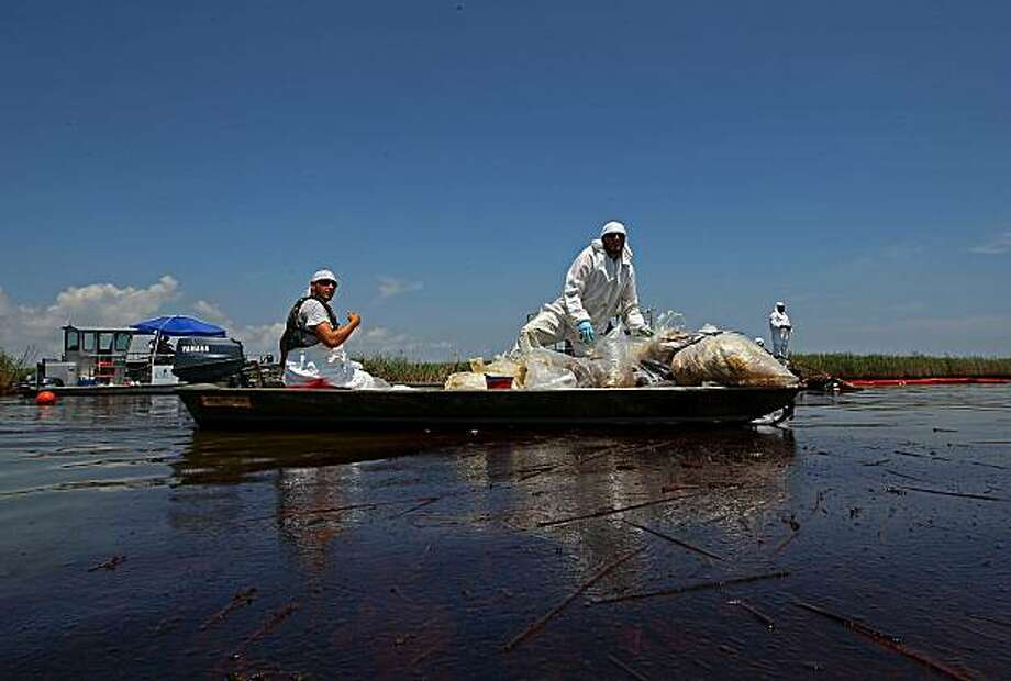 "VENICE, LA - JUNE 01:  Contract workers from BP ferry oil soaked waste to a pickup point as other workers use skimmers to clean oil from a marsh near Pass a Loutre on June 1, 2010 near Venice, Louisiana. Earlier in the day, U.S. President Barack Obama called the Deepwater Horizon accident the ""greatest environmental disaster of its kind in our history."" Photo: Win McNamee, Getty Images"