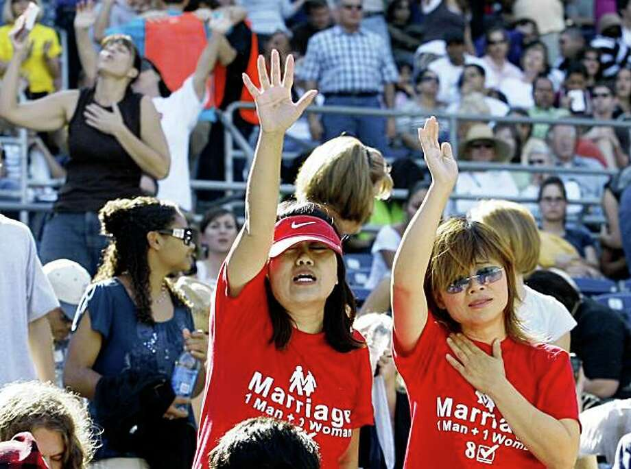 """Wearing T-shirts supporting California Proposition 8 Chiffon Frey,front  left, and Jennifer Post, right, pray during a """"Yes on 8"""" prayer event held at Qualcomm Stadium in San Diego Saturday, Nov. 1, 2008. Thousands took part in the 12-hour prayer and fasting event. The  ballot initiative would ban same-sex marriage in California.  (AP Photo/Denis Poroy) Photo: Denis Poroy, AP"""