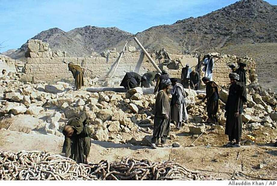 Afghan men work on a house destroyed in alleged airstrikes in Shah Wali Kot district of Kandahar province, south of Kabul, Afghanistan, Wednesday, Nov. 5, 2008. Afghan President Hamid Karzai said airstrikes had caused deaths in the district. The U.S. military said it was investigating the report. (AP/Photo/Allauddin Khan) Photo: Allauddin Khan, AP