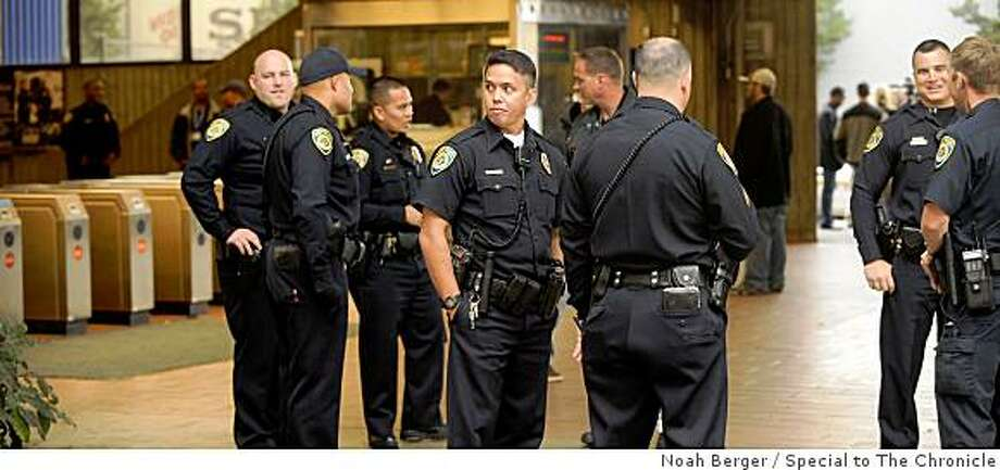 BART police officers stand watch at the Fruitvale BART station shortly after protesters jumped the fare gates.  The youths were en route to a San Francisco rally against immigration raids. Photo: Noah Berger, Special To The Chronicle
