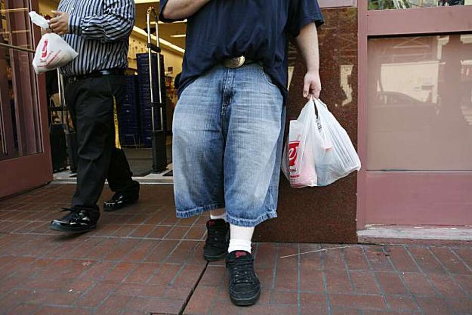 Luther Carr, (right) of San Francisco, holds newly purchased goods in a non-biodegradable plastic Walgreens bag front of the 850 Market Street store on Monday May 19, 2008 in San Francisco, Calif. On Monday some of the bags being used where non-recyclable while others were. The store is in the process of phasing out non-degradable plastic bags in preparation for the city-wide ban on them starting May 20, 2008. Photo by Mike Kepka / San Francisco Chronicle Photo: Mike Kepka, The Chronicle