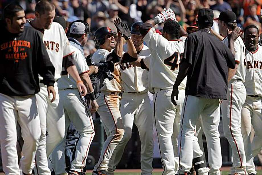The Giants mob Andres Torres after his game-winning single scored Juan Uribe in the bottom of the tenth inning in San Francisco on Sunday. Photo: Carlos Avila Gonzalez, The Chronicle