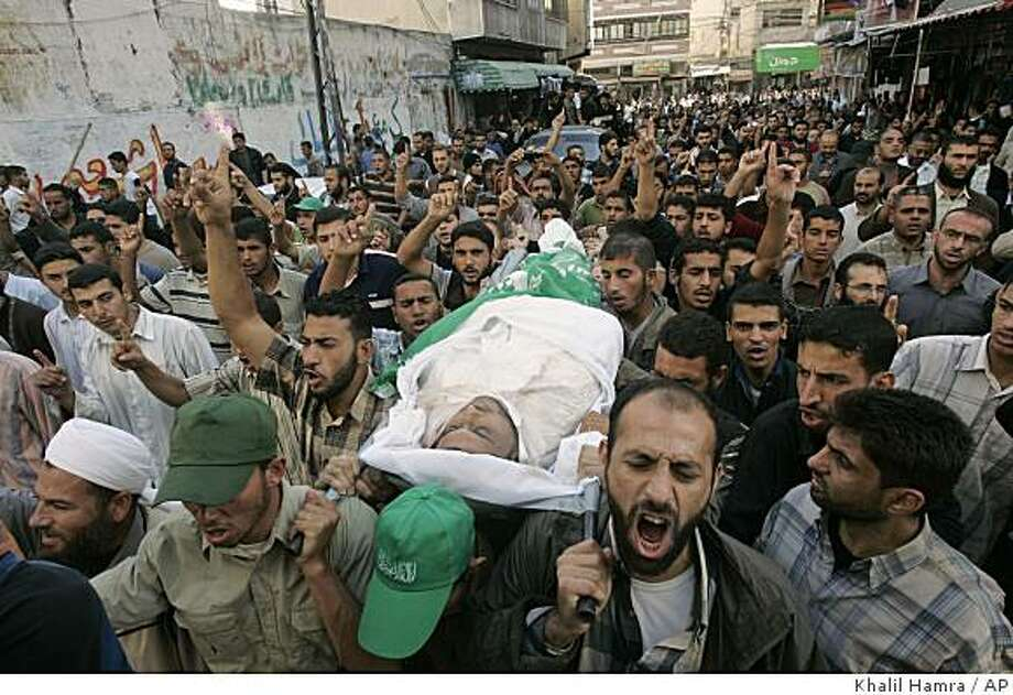 Palestinian mourners chant slogans as they carry the body of one of four Hamas militants killed in a early morning Israeli missile attack, during their funerals in Khan Younis refugee camp, southern Gaza Strip, Wednesday, Nov. 5, 2008. Hamas militants pounded southern Israel with a barrage of rockets Wednesday, hours after Israeli forces killed six gunmen, a fresh bout of violence that threatened to unravel a five-month-old truce that has brought relief to both Gaza and southern Israel. The clashes began late Tuesday after the Israeli army burst into Gaza to destroy what it said was a tunnel being dug near the border to abduct Israeli troops. (AP Photo/Khalil Hamra) Photo: Khalil Hamra, AP