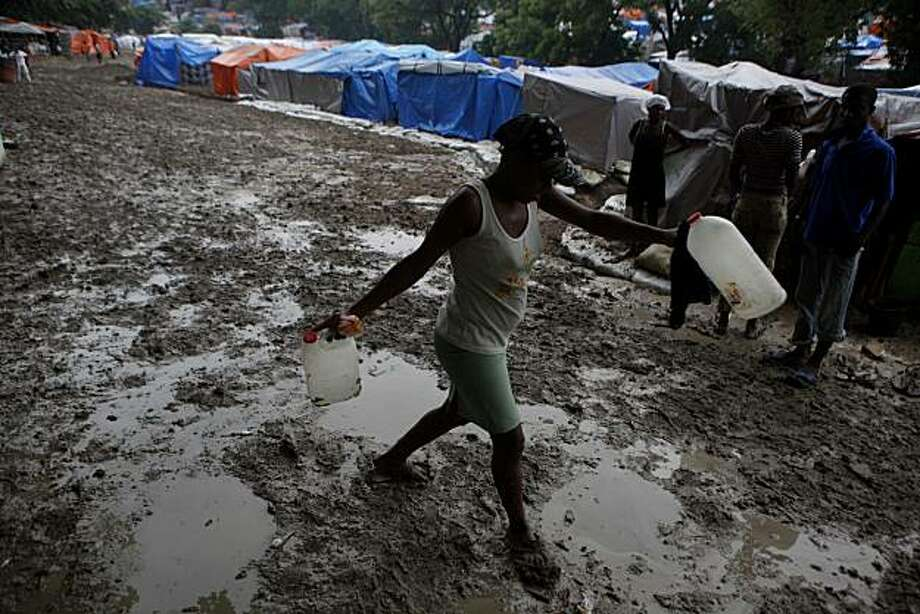 A woman carries water bottles inside a camp for earthquake displaced people after a rain in Port-au-Prince, Friday, May 28, 2010. A hurricane season predicted to be one of the wettest on record opens officially on June 1st in the Caribbean, where hundredsof thousands of Haitian earthquake victims have only tarps or fraying tents to protect them in a major storm. Photo: Esteban Felix, AP