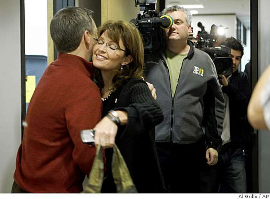 Alaska Gov. Sarah Palin, followed by media, gives Lt. Gov. Sean Parnel a hug after she arrived at her office in Anchorage, Alaska on Friday, Nov. 7, 2008, for the first time since she began campaigning as Sen. John McCain's vice presidential running mate. (AP Photo/Al Grillo) Photo: Al Grillo, AP