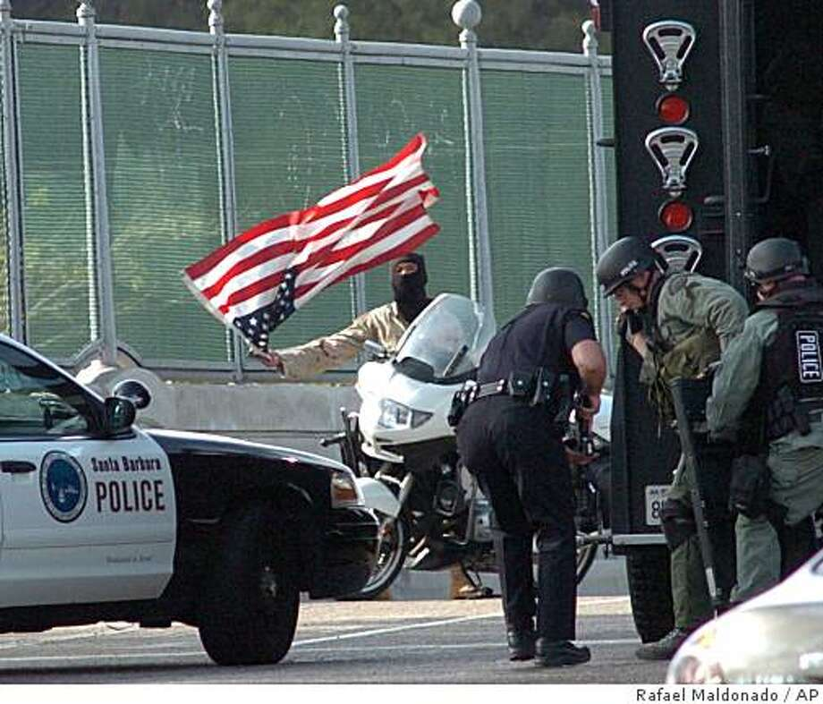 ** ADDS IDENTITY OF SUBJECT ** Police negotiate with a man identified by police as Eddie Vantassel, 28, an Iraqi War Veteran, dressed in army fatigues holding a gun and waving an American flag on an overpass across Highway 101, closing the major highway for hours in Santa Barbara, Calif. on Monday Nov. 3, 2008. Police say the man appeared to have an anti-war sentiment. (AP Photo/Santa Barbara News-Press, Rafael Maldonado) Photo: Rafael Maldonado, AP