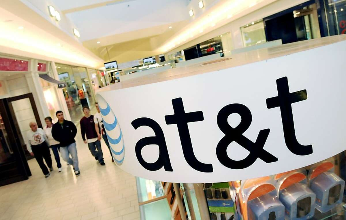 FILE - In this file photo made Oct. 20, 2009, people walk through the Northshore Mall beyond near an AT&T kiosk, in Peabody, Mass. AT&T Inc. will stop letting new customers sign up for its unlimited Internet data plan for smart phones and iPads, hoping toease congestion on its network by charging the people who use the most data more.