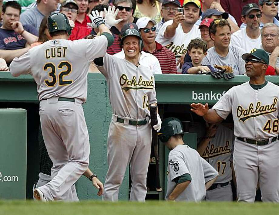 Oakland Athletics' Jack Cust, left, is welcomed into the dugout by teammate Mark Ellis, center, and Athletics bench coach Tye Waller, right, after hitting a home run off a pitch by Boston Red Sox's Manny Delcarmen in the eighth inning of a baseball game at Boston's Fenway Park, Thursday, June 3, 2010. The Athletics defeated the Red Sox 9-8. Photo: Steven Senne, AP
