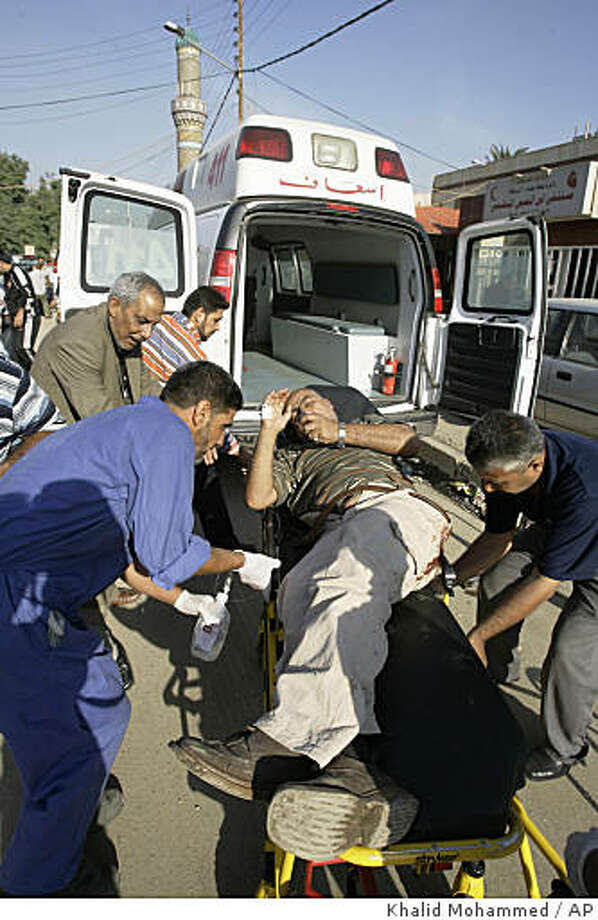 An injured man is transported to Ibn al-Nafees hospital, after a bomb explosion in Baghdad, Iraq, on Monday, Nov. 3, 2008.  Two bombs, one of them hidden in a trash can, exploded in a central Baghdad square Monday, killing six people and wounding 21 others, police said. (AP Photo/Khalid Mohammed) Photo: Khalid Mohammed, AP