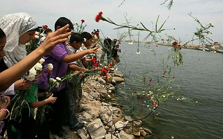 Palestinian children throw flowers in the sea at Gaza City's port on June 1, 2010, during a ceremony in memory of the activists killed in a deadly Israeli raid on a Gaza-bound humanitarian aid flotilla on May 31, 2010. Photo: Mahmud Hams, AFP/Getty Images