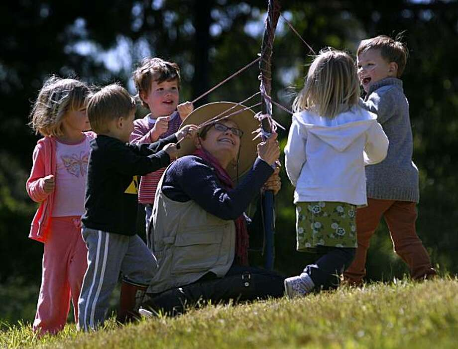 Teacher Linda Constant holds a maypole for students in the Nature Nurture outdoor preschool program at The Presidio in San Francisco, Calif., on Tuesday, May 11, 2010. Photo: Paul Chinn, The Chronicle