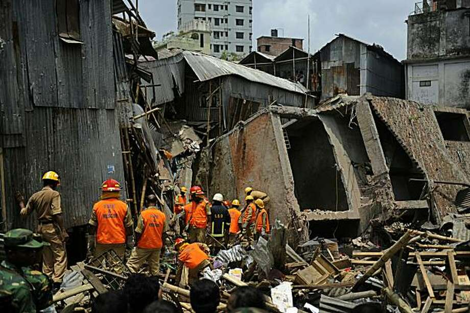 Bangladehsi firefighters search through the rubble of a collapsed building in Dhaka on June 2, 2010. At least 14 people were killed and 25 injured when a four-storey building collapsed onto tin-roofed shanties in the Bangladeshi capital Dhaka, police andofficials said. Photo: Munir Uz Zaman, AFP/Getty Images