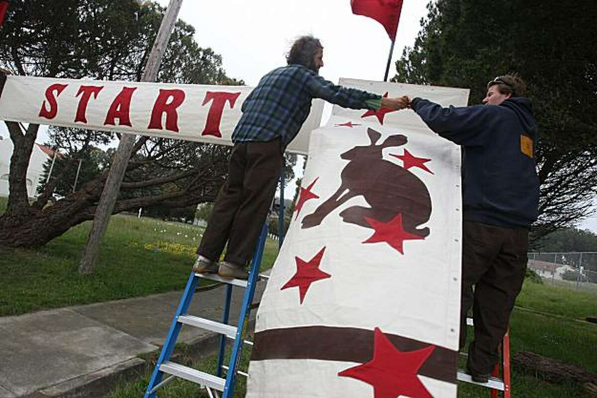 Artist Nathan Lynch (right) stitched together the banners for his installation and is hanging them with the help of artist Michael Swaine (left) at Fort Winfield Scott in the Presidio in San Francisco, Calif., on Friday, May 14, 2010. Lynch is one of 10 artists building installations for Presidio Habitats. His is the start and finish line for an imaginary race between a turtle and a hare.