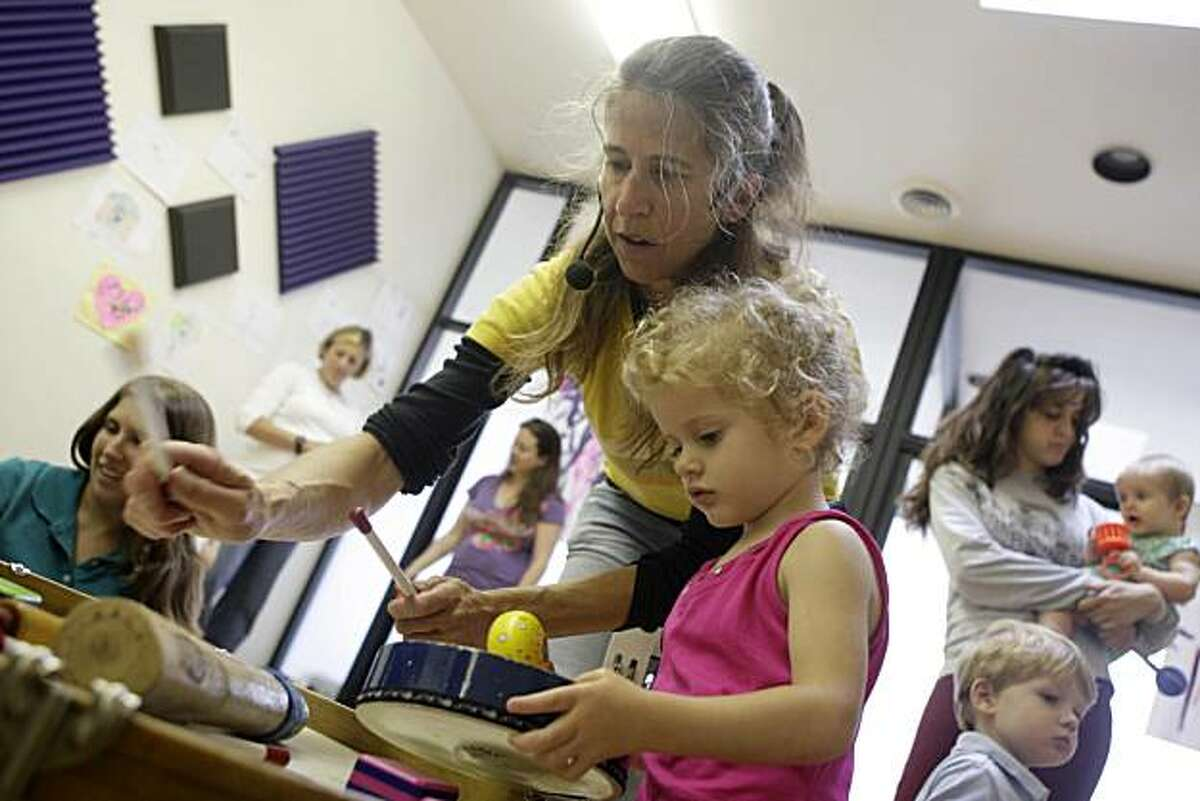 Charity Kahn (center) beats a rhythm on a drum as Lourdes Smith, 21 months, of San Francisco and others in the class play instruments during Kahn's Jamboodas Classic class at the JAMspace in San Francisco, Calif. on Tuesday May 18, 2010. Charity Khan is a children's music performer and songwriter who has received royalties from her exposure in internet and satellite radio since 2008.