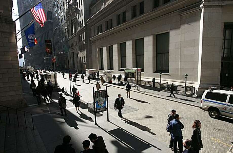 FILE - In this file photo taken March 9, 2010, people walk on Wall Street, in New York. Stocks appear set to end a volatile month with a quiet day ahead of the Memorial Day weekend. Futures traded in a narrow range Friday, May 28, 2010, after the major indexes surged a day earlier. Photo: Mark Lennihan, AP