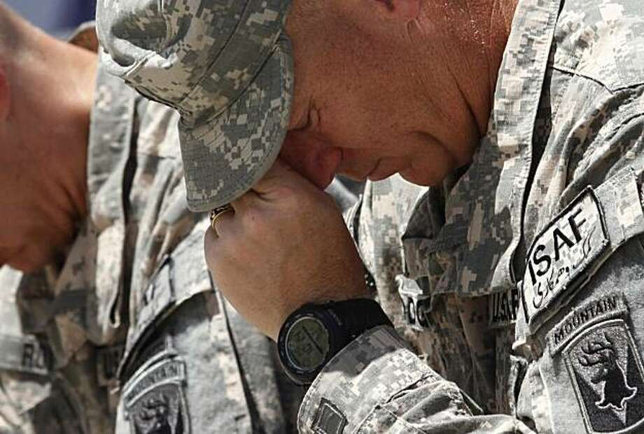 A U.S soldier observes a moment of silence during a ceremony marking Memorial Day at the main U.S. base in Bagram, north of Kabul, Afghanistan, Monday, May 31, 2010. The U.S. military death toll in the Afghan conflict reached the 1,000 mark on May 28, 2010. Photo: Musadeq Sadeq, AP