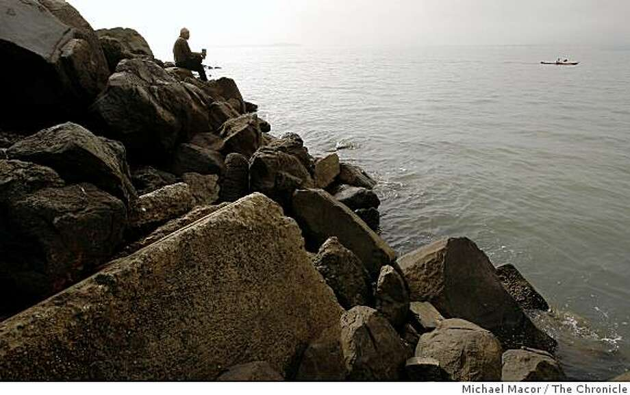 Yogi Veda, left of Berkeley enjoys early morning on the rip-rap at the edge of San Francisco Bay on the Berkeley Marina shoreline on Tuesday Oct. 28, 2008. The area was hit hard after last years' oil spill when the cargo ship Cosco Busan ran into the suspension tower of the Bay Bridge and spilled 58,000 gallons of bunker fuel. Little evidence of the damage caused by the spill is visible. Photo: Michael Macor, The Chronicle