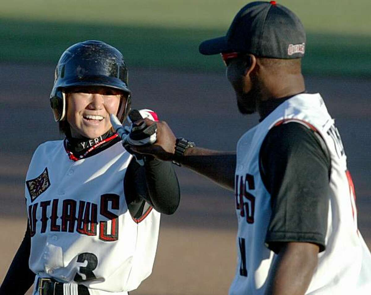 Chico Outlaws female knuckleballer Eri Yoshida (left) bumps knuckles with first base coach Garry Templeton Jr. after knocking a RBI single against the Tijuana Cimarrones in the bottom of the first inning during their GBL baseball game at Nettleton Stadium May 29, 2010 in Chico, Calif.