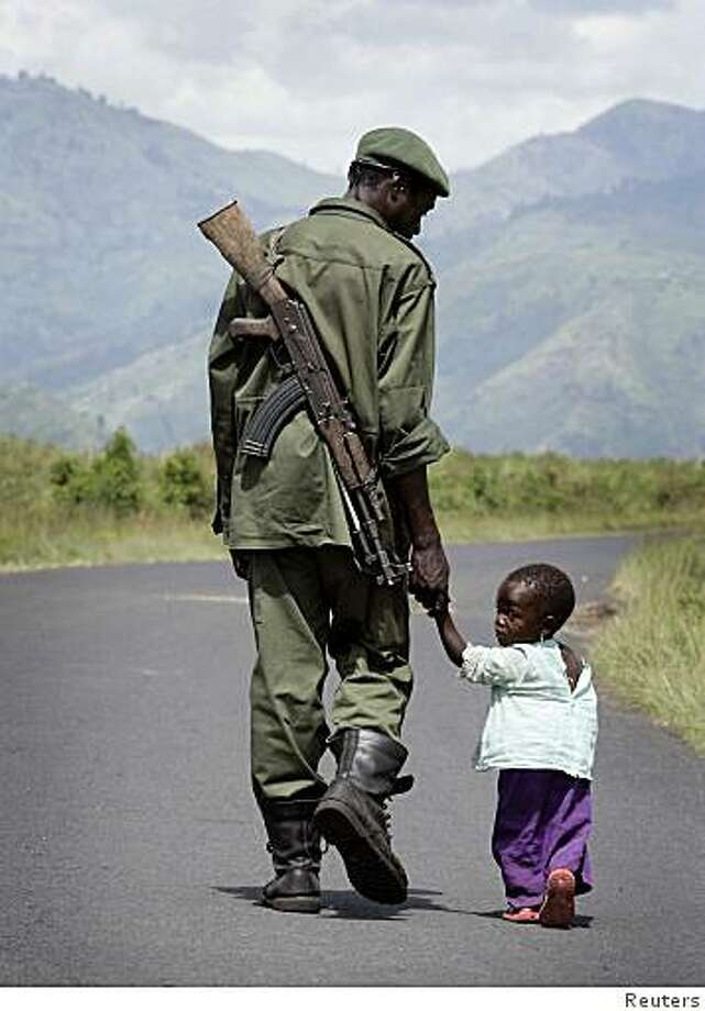A Congolese Government soldier walks on the road towards Sake holding his daughter's hand, near the city of Goma in eastern Congo, November 4, 2008. Tutsi rebels clashed with a local militia group in eastern Democratic Republic of Congo on Tuesday, the U.N. said, adding its own peacekeepers were in the crossfire between the factions. REUTERS/Stringer (DEMOCRATIC REPUBLIC OF CONGO) Photo: STR, Reuters