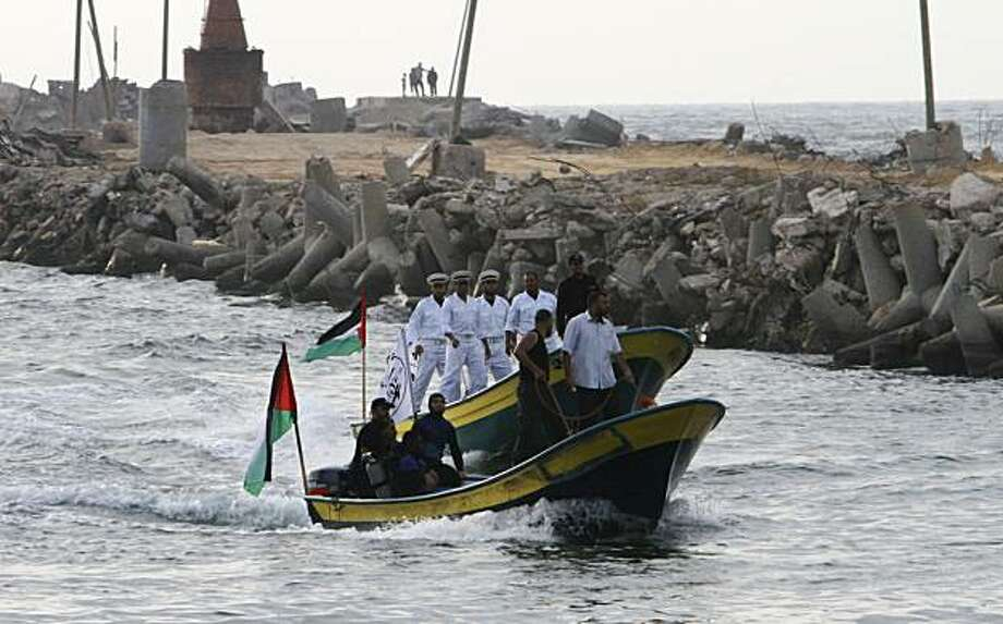 """Palestinian members of the Hamas naval police and civilian defense officers ride a boat at Gaza port during a display of their preparations ahead of the expected arrival of a flotilla of hundreds of pro-Palestinian activists trying to sail into the Gaza Strip, in Gaza city, Friday, May 28, 2010. Israel's foreign minister Avigdor Lieberman says the country is prepared to stop a flotilla of the pro-Palestinian activists from reaching the Gaza Strip """"at any cost"""". Greta Berlin, one of the organizers of the effort, said a total of seven ships carrying hundreds of volunteers are now on their way to Gaza. They are expected to reach the Israeli coast on Saturday. Photo: Adel Hana, AP"""