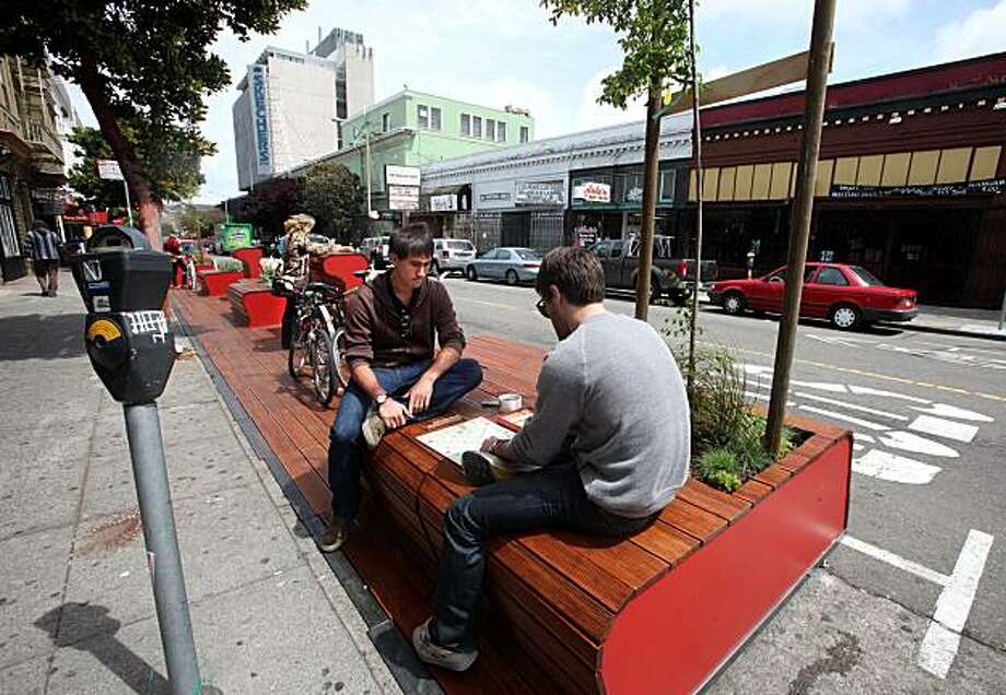 "Rohan Ma (middle) from Chicago, and Jared Press (right) from San Francsico play scrabble at the 22nd Street Parklet in San Francisco, Calif., on Wednesday, May 12, 2010.  Put in a few days ago, the ""Pavement to Parks"" project repurposed three parking spaces to provide new public space. Photo: Liz Hafalia, The Chronicle"