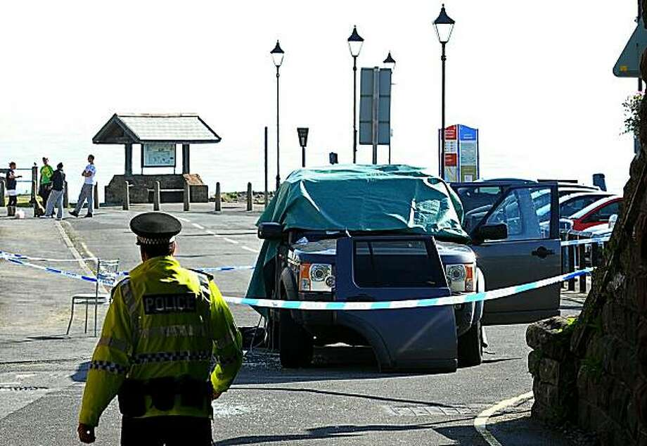 "A police officer walks past a car that was shot at in Seascale, Cumbria, north west England on June 2, 2010. on June 2, 2010.   A gunman killed at least 12 people after going on a rampage in a popular tourist area in northwest England on Wednesday, beforeapparently turning the gun on himself, police said.  ""We can... confirm that from our current indications 12 people have lost their lives, plus Derrick Bird (the gunman),"" said Deputy Chief Constable Stuart Hyde of the local police at a press conference. Photo: Andrew Yates, AFP/Getty Images"