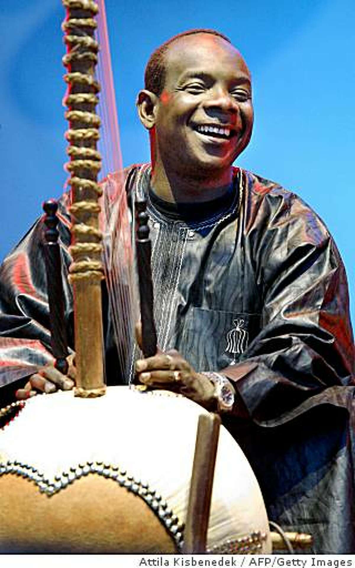 Budapest, HUNGARY: Toumani Diabate of Mali plays on his kora, an African harp on the 'World Music' stage of Island Festival in Hajogyar Island of Budapest, late 11 August 2006. With 550 concerts on 66 stages over seven days, featuring everything from pop to gypsy music, the yearly 14th Sziget Festival is expecting to draw some 400,000 music lovers to converge on an island in the middle of the Danube river, in the heart of Budapest from 09 August to 16 August. AFP PHOTO ATTILA KISBENEDEK (Photo credit should read ATTILA KISBENEDEK/AFP/Getty Images)