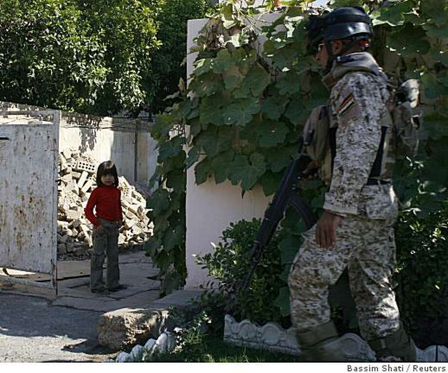 A girl looks at an Iraqi soldier on patrol in Baghdad November 2, 2008. The Iraqi army arrested two suspected insurgents and confiscated weapons from them during a search military operation in Baghdad.  REUTERS/Bassim Shati (IRAQ) Photo: Bassim Shati, Reuters