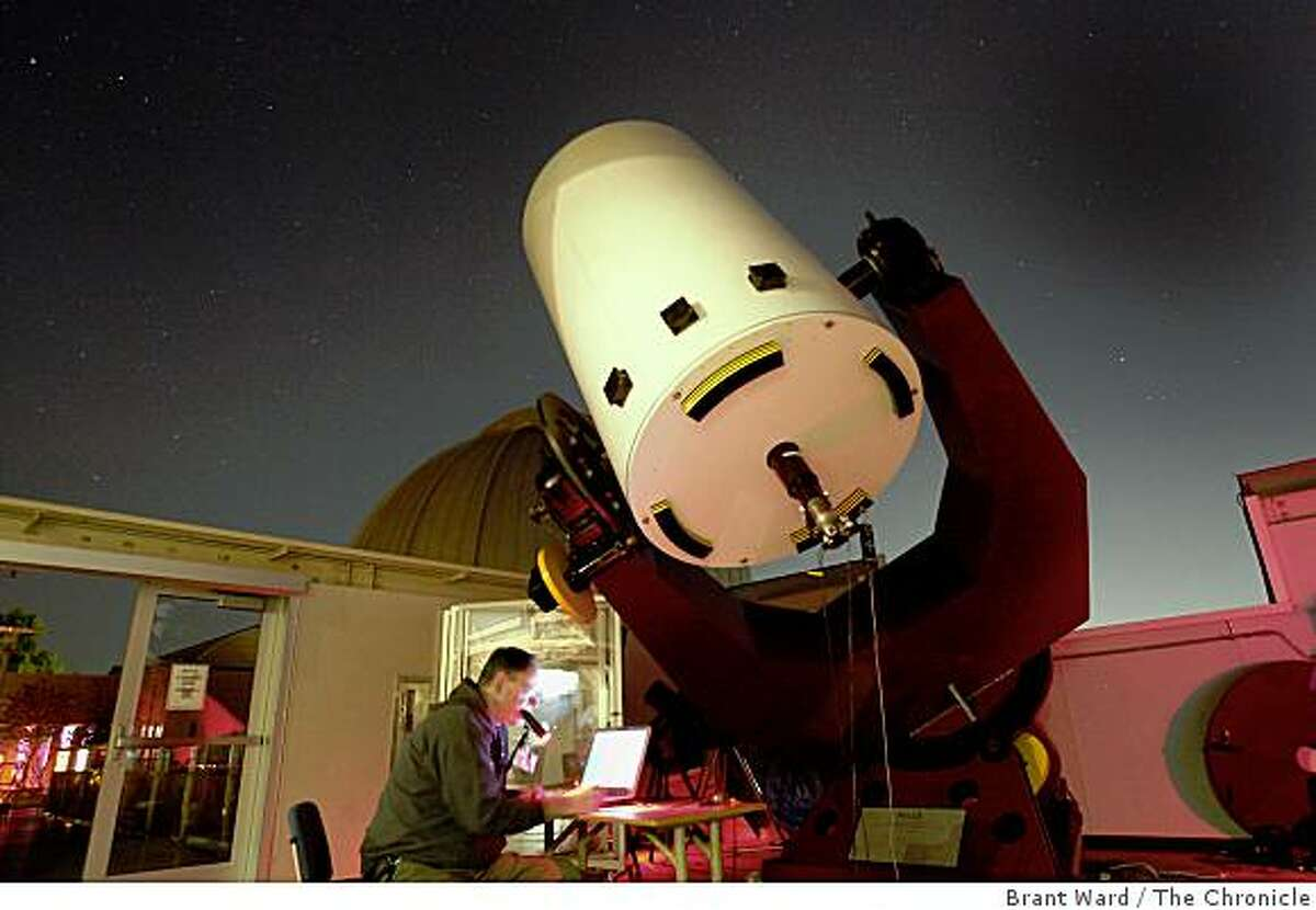 Astronomer Gerald McKeegan looks over his computer as he analyzes photos taken of asteroids. Two official trackers of wayward asteroids, Gerald McKeegan and Conrad Jung, gather at the Chabot Space and Science observatory every couple weeks to watch and track asteroids Wednesday October 22, 2008.