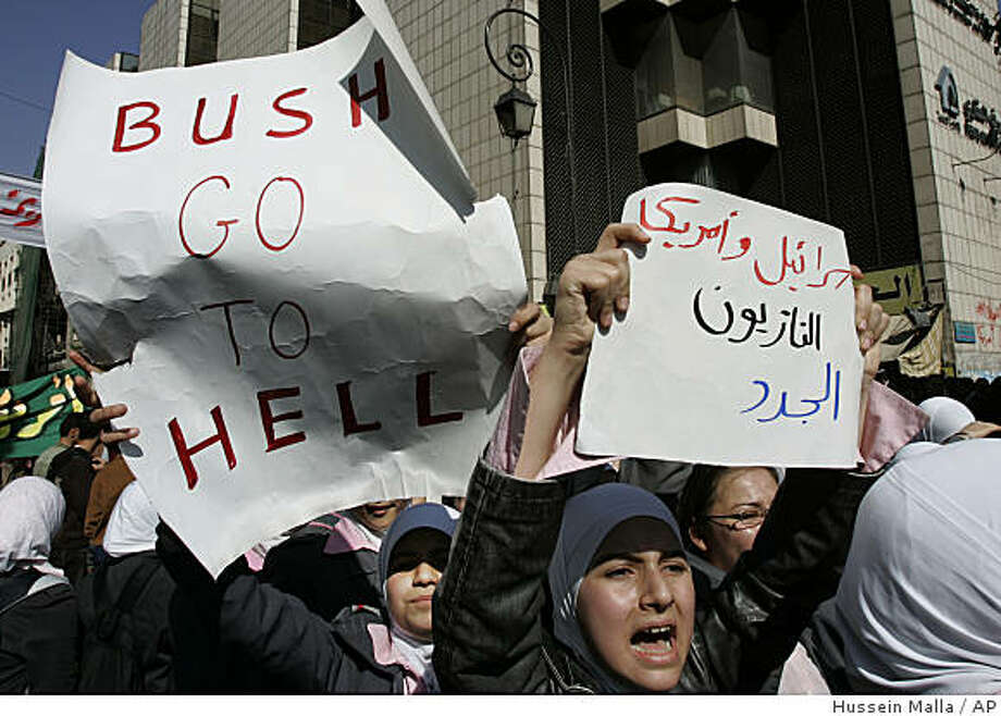 """Syrian student protesters holds a placard against the United States President George W. Bush, as other one holds an Arabic placard reads:""""The American and the Israeli are the new Nazis,"""" during a demonstration against the U.S. raid on a village near the Syrian-Iraqi border, in Damascus, Syria, on Thursday Oct. 30, 2008. Hundreds of Syrian riot police ringed the shuttered and closed U.S. Embassy in Damascus on Thursday, as tens of thousands of Syrians converged on a central square for a government-orchestrated protest to denounce a deadly U.S. raid near the Iraqi border.(AP Photo/Hussein Malla) Photo: Hussein Malla, AP"""
