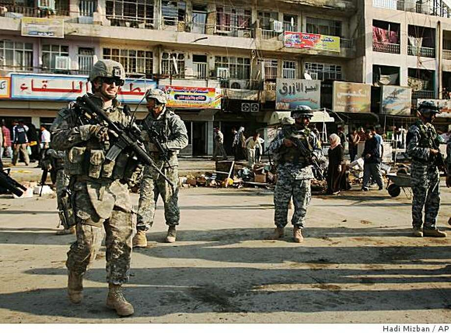 U.S and Iraqi army soldiers secure the area at the scene were bombs exploded, in Baghdad, Iraq on Tuesday, Nov. 4, 2008. Bombs exploded at a bus station and a small market in Baghdad, killing 15 people and wounding 29 others Tuesday, police and hospital officials said. Violence has dropped in Iraq since the U.S. military and Iraqi security forces have gained the upper hand against insurgents, but scattered attacks still occur almost daily. (AP Photo/Hadi Mizban) Photo: Hadi Mizban, AP