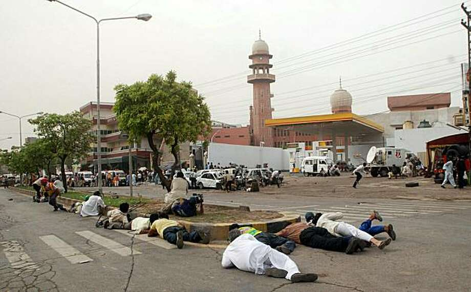 Pakistani media take cover outside one of two mosques stormed by gunmen in Lahore on May 28, 2010. Gunmen wearing suicide vests stormed two Pakistani mosques belonging to a minority sect in Lahore, bringing carnage to Friday prayers and killing around 80people, officials said. Squads of militants burst into prayer halls firing guns, throwing grenades and taking hostages in the deadliest attack on the city of eight million, which has been increasingly hit by Taliban and Al-Qaeda-linked violence. Photo: Arif Ali, AFP/Getty Images