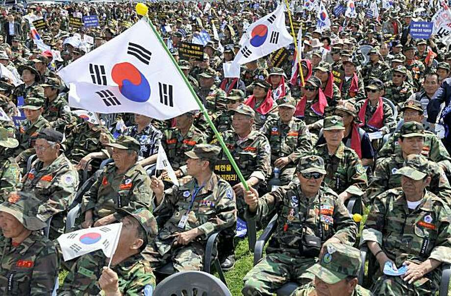 South Korean veterans wave national flags during a rally against North Korea for the sinking of a South Korean warship in downtown Seoul on May 27, 2010. North Korea scrapped a pact aimed at preventing accidental armed clashes with South Korea at their flashpoint border, as tempers flared in both countries over the sinking of a warship. Photo: Jung Yeon-je, AFP/Getty Images
