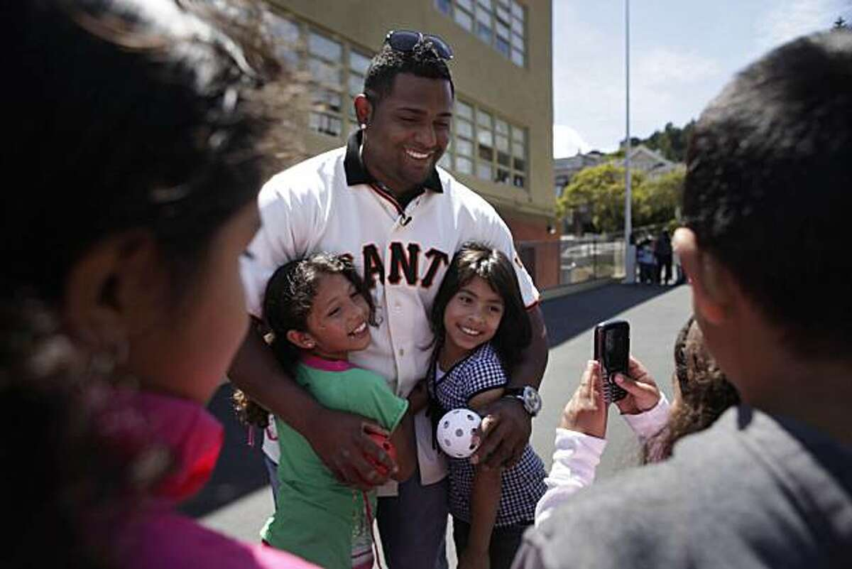 Giants' infielder Pablo Sandoval gets a hug from Stacy Salazar, 8 (left in green) and Evelyn Maldonado, 8,during an appearance at the Mission Education Center. Sandoval appeared at the Mission Education Center in the first of a series of Operation Panda events encouraging kids to be active in the summer in San Francisco, Calif. on Wednesday May 26, 2010.