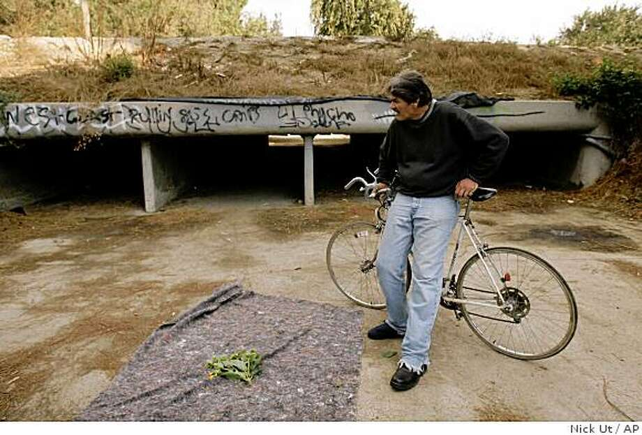 Don Morgan, who said he was a friend of the five homeless victims who were found shot to death in a homeless encampment, looks at the scene Monday, Nov. 3,  2008, in Long Beach, Calif.  The bodies of three men and two women were found Sunday in the space between commercial buildings and Interstate 405 in Long Beach, police said. (AP Photo/Nick Ut) Photo: Nick Ut, AP
