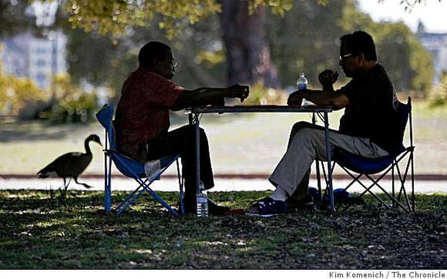 Domino players Howard Allmon, left, and Willie Hendricks, both of Oakland, Calif., find a shady spot near Oakland's Lake Merritt in Oakland,Calif., on Sept. 3, 2008. Photo: Kim Komenich, The Chronicle