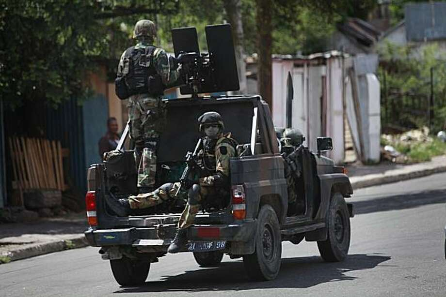 Soldiers patrol blocks away from the Tivoli Gardens neighborhood, Kingston, Wednesday, May 26, 2010.  According to the the country's official ombudsman, at least 44 civilians have been killed as Jamaican security forces have moved into the slum strongholdof a gang leader sought by the U.S. justice yet he remains at large after nearly 3 days of street battles. Photo: Rodrigo Abd, Associated Press