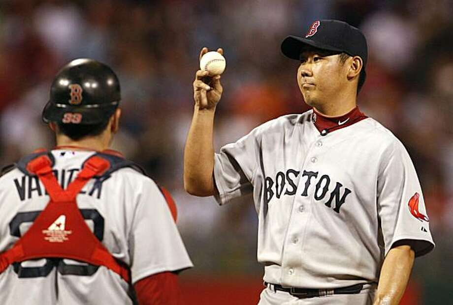 Boston Red Sox pitcher Daisuke Matsuzaka, right, jiggles the ball, and then asks for a new one after the Philadelphia Phillies' Juan Castro broke up his no-hitter in the eighth inning. The Red Sox defeated the Phillies, 5-0, at Citizens Bank Park in Philadelphia, Pennsylvania, Saturday, May 22, 2010. (Ron Cortes/Philadelphia Inquirer/MCT) Photo: Ron Cortes, MCT