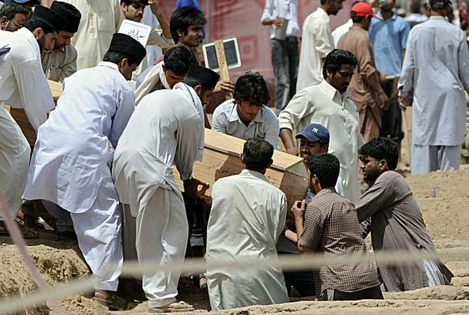 Ahmadi Pakistanis burry a victim of yesterday's religious attack at an Ahmadi graveyard in Rabwa on May 29, 2010, a spiritual centre for the Ahmadi community in Pakistan about 160 kilometre west of Lahore. Victims of deadly May 28 attacks on two Pakistanimosques were buried separately after community members cancelled a mass funeral for more than 80 people, fearing further attacks. Photo: Farooq Naeem, AFP/Getty Images