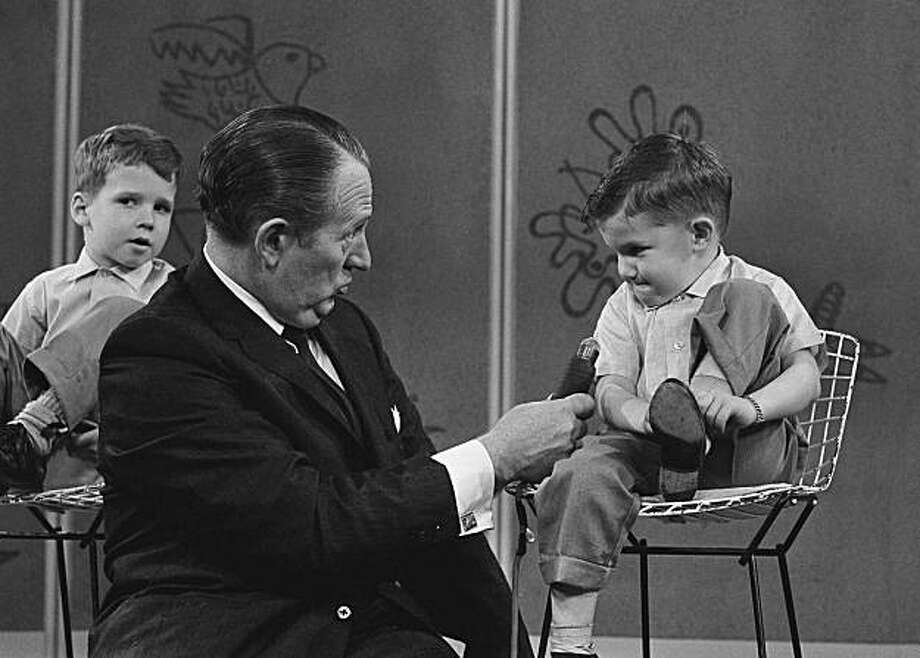 """In this April 5, 1962 file photo, TV personality Art Linkletter talks with 4-year-old Ronnie Glahn shows Art Linkletter his idea of how bad guys look, on Art's TV show in Hollywood, April 5, 1962 in Los Angeles.  Linkletter, who hosted the popular TV shows """"People Are Funny"""" and """"House Party"""" in the 1950s and 1960s, died Wednesday, May 26, 2010 at his home in the Bel-Air section of Los Angeles.  He was 97. Photo: David F. Smith, AP"""