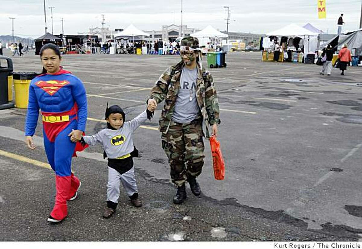 Festivalgoers in thier costumes (l-r) April Garguena, her son Jaden Badilla and Emmalou Gonzales walk through the grounds of the San Francisco Halloween Festival in the parking lot at AT&T park in San Francisco, Calif., on Friday, Oct 31, 2008.