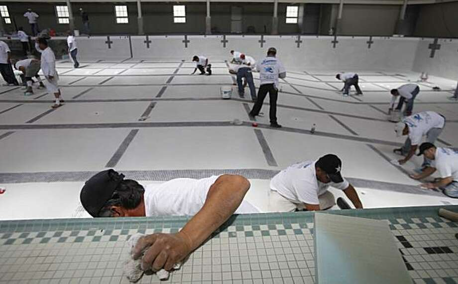 Serrano Pool and Plaster employee, Simon Becerra joins other workers to apply the final plastering coat at the newly renovated Richmond Plunge on Thursday May 13, 2010 in Richmond, Calif. The public superpool is a massive 160 feet by 60 feet and set to open sometime in July. Photo: Mike Kepka, The Chronicle