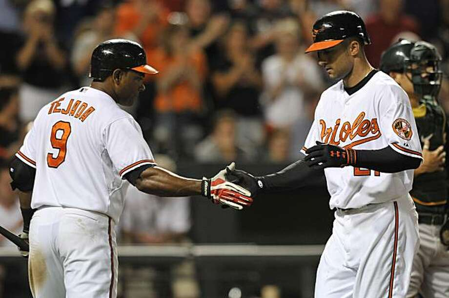 Baltimore Orioles Nick Markakis is congratulated by Miguel Tejada after hitting a solo home run against the Oakland Athletics in the eighth inning of a baseball game Tuesday, May 25, 2010 in Baltimore. The Orioles won 5-1. Photo: Gail Burton, AP