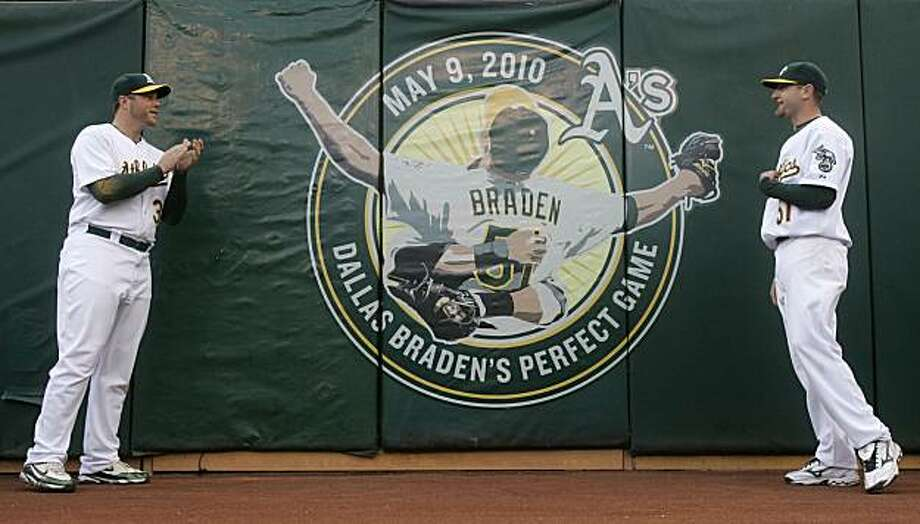 Oakland Athletics catcher Landon Powell, left, and pitcher Dallas Braden are shown near a logo commemorating Braden's perfect game before a  baseball game against the San Francisco Giants in Oakland, Calif., Friday, May 21, 2010. Photo: Jeff Chiu, AP