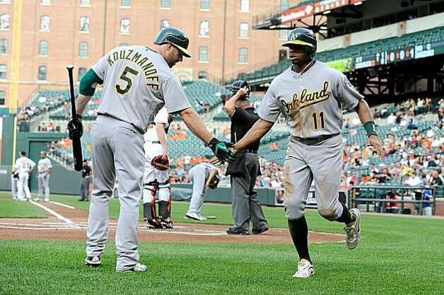 BALTIMORE - MAY 26:  Rajai Davis #11 of the Oakland Athletics is congratulated by Kevin Kouzmanoff #5 after scoring in the first inning against the Baltimore Orioles at Camdem Yards on May 26, 2010 in Baltimore, Maryland. Photo: Greg Fiume, Getty Images
