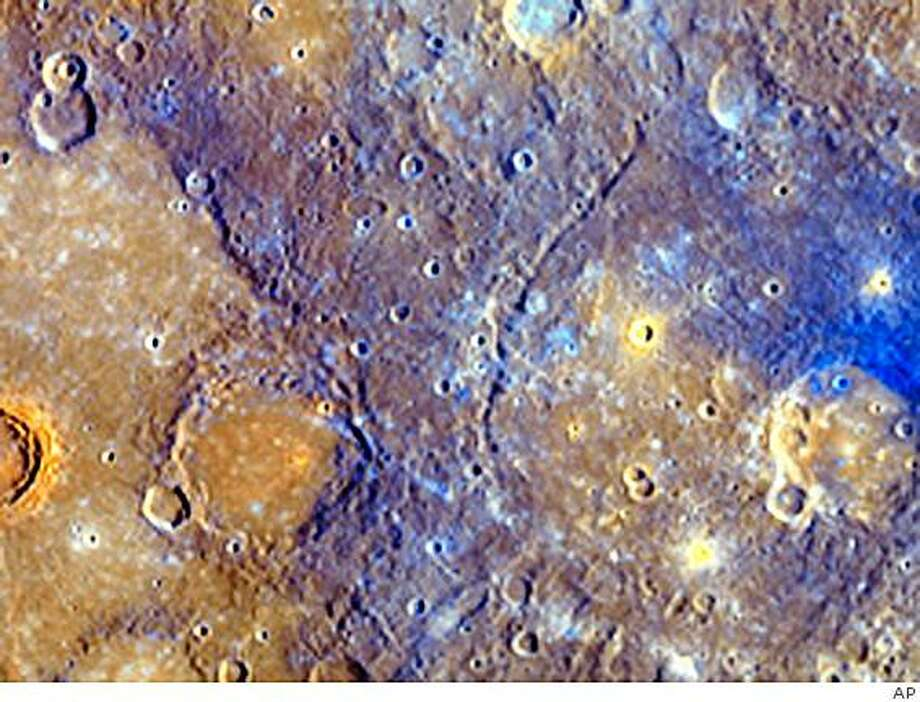 "This undated handout photo provided by NASA, taken earlier this month by the Messenger space probe, shows a portion of Mercury. Earth's first nearly full look at Mercury reveals that the tiny lifeless planet took a far greater role in in shaping itself than scientists had thought with volcanoes spewing ""mysterious dark blue material."" (AP Photo/NASA) Photo: AP"