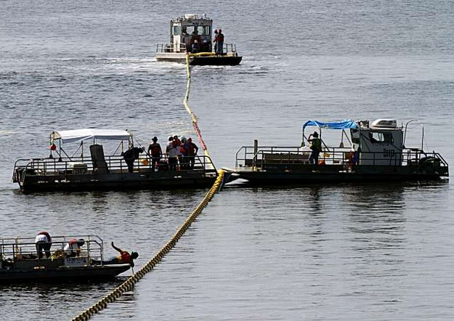 Workers deploy oil containment booms in the Bay of St. Louis in Biloxi, Mississippi, on Wednesday, May 19, 2010. The containment booms are being put out to protect the area from the Deepwater Horizon oil spill. (John Fitzhugh/Biloxi Sun-Herald/MCT) Photo: John Fitzhugh, MCT